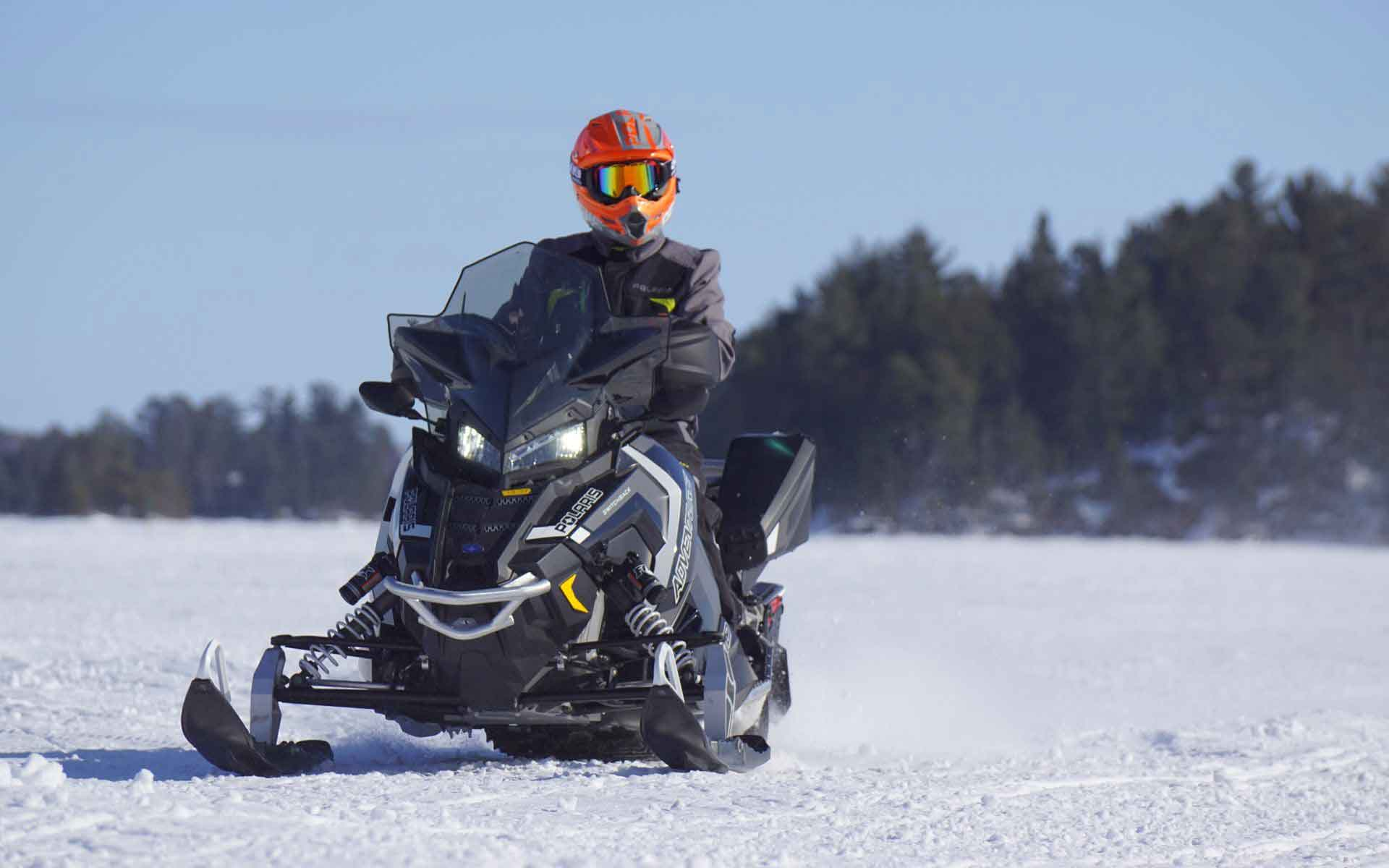 person riding a snowmobile on a snowy lake
